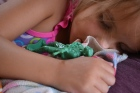 A girl sleeping with a plastic green army figurine